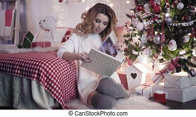 Beautiful brunette looking at photo album near Christmas tree