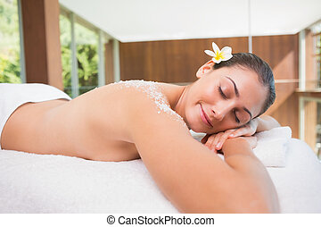 Beautiful brunette lying on massage table with salt scrub on bac