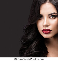 Beautiful brunette model: curls, classic makeup and red lips. The beauty face.