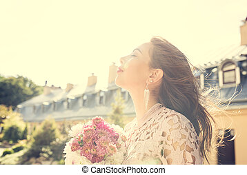 Beautiful brunette model in pink dress with flowers in hands on a background of city. Vintage toning effect