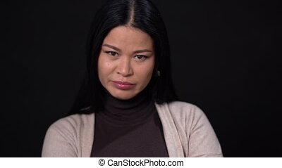 Asian Woman on a Black Background with Dark Hair and Narrow Eyes. She is Surprised and Saddened by this. She is Wearing a Brown Sweater and a Beige Cardigan. Asian beauty concept. Close Up Shoot.