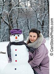 Beautiful brunette near a snowman