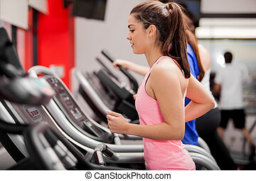 Cute young Latin woman exercising on a treadmill at a gym