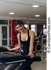 Beautiful brunette on a treadmill