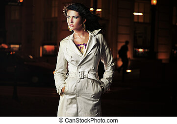 Beautiful brunette over a night city background