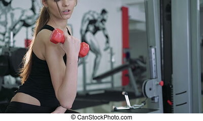 Beautiful brunette performs an exercise with dumbbells. 4k