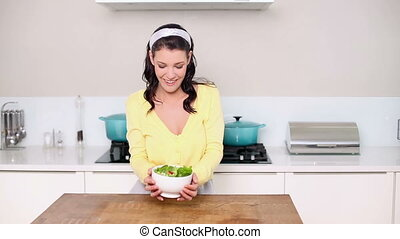 Beautiful brunette picking up a bowl of salad in the kitchen...