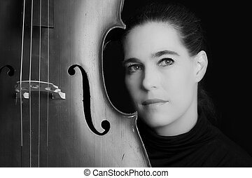 Beautiful brunette playing a cello with selective light in...