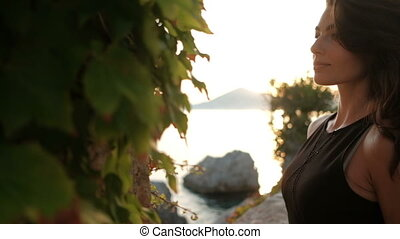 Beautiful brunette poses on sea shore on summer evening...
