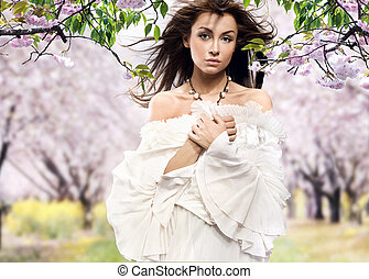 Beautiful brunette posing in cherry orchard