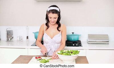 Beautiful brunette preparing a salad