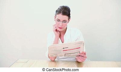 Beautiful brunette reading the news