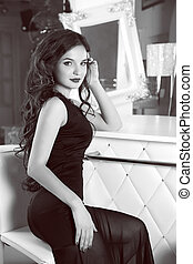 Beautiful brunette sexy woman model in black elegant dress sitting on chair by counter top in modern white interior. Long wavy hair style. Makeup.