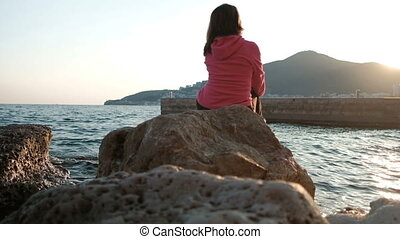 Beautiful brunette sits back on the rocks near lake in her travel.
