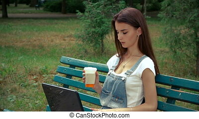 beautiful brunette sits on the bench and watching in a laptop