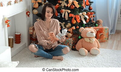 beautiful brunette sitting near a Christmas tree with toys and smiles