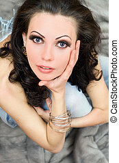 Beautiful brunette sitting on grey fur