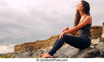Beautiful brunette sitting on the rocks