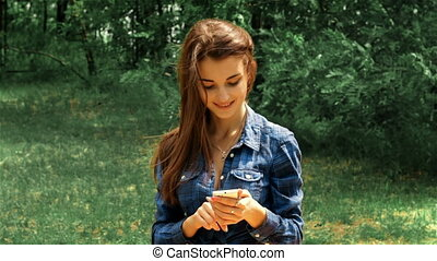 beautiful brunette sitting on the street and look in the phone