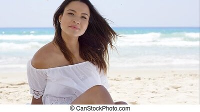 Beautiful brunette smiles at camera on beach
