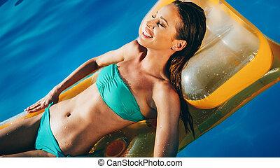 Beautiful brunette swimming in pool