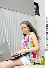 Beautiful brunette teen little girl laptop city