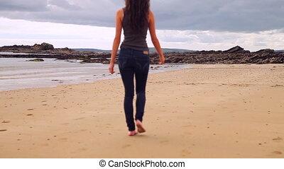 Beautiful brunette walking along the water