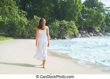 Beautiful brunette walking among the seacoast leaving ...