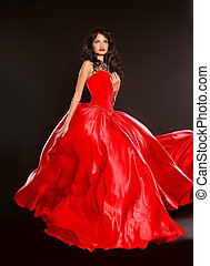 Beautiful brunette wearing in blowing red dress isolated on black background