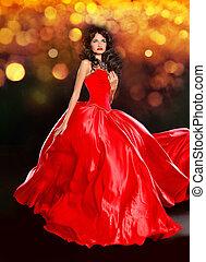 Beautiful brunette wearing in luxury red dress over dark golden bokeh background.