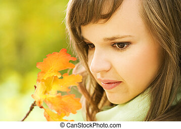 Beautiful brunette with autumn leaves close-up portrait