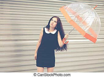 Beautiful brunette with long hair in a short black with an umbrella in her hands looking at the sky waiting for the rain. Colorful hipster photo