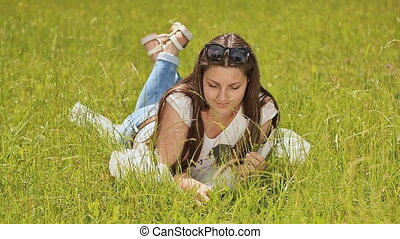 Beautiful brunette with long hair lying on green grass with a smile and enjoy nature.