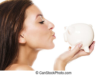 beautiful brunette woman about to kiss a white piggy bank on white background