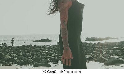 Beautiful brunette woman in black silky dress walking, running, flirting with the camera at the beach during summer day - video in slow motion