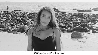 Portrait of beautiful brunette woman in black silky dress walking, running, flirting with the camera at the beach during summer day - black and white video in slow motion