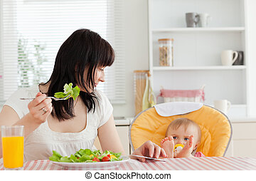 Beautiful brunette woman eating a salad next to her baby while sitting in the kitchen