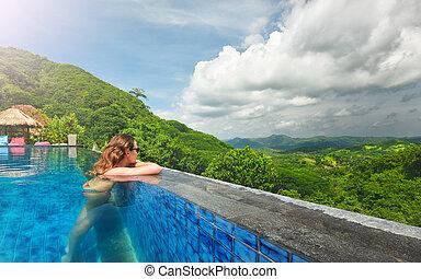 Beautiful brunette woman enjoying relax in spa pool at resort.