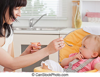 Beautiful brunette woman feeding her baby while sitting