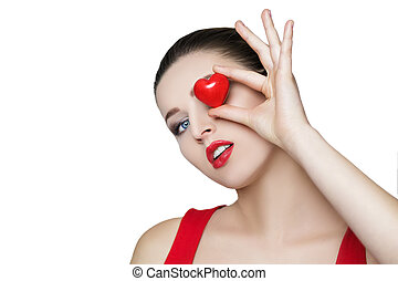 beautiful brunette woman holding red heart in front of the face.
