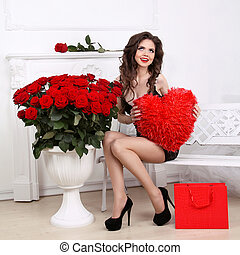 Beautiful Brunette Woman holding red heart over bouquet of roses. Valentine girl. Beauty Glamour Fashion model portrait. Valentine's day love concept.