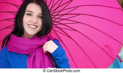 Beautiful brunette woman holding red umbrella