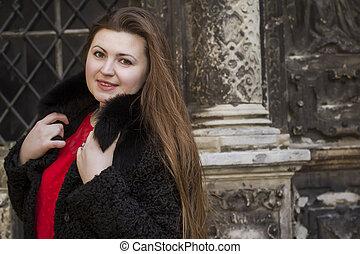 Beautiful brunette woman in a black fur coat