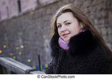 Beautiful brunette woman in a fur coat