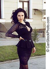 Beautiful brunette woman in black dress, outdoors