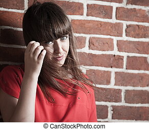 Beautiful brunette woman in front of a brick wall