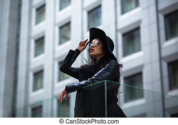 Beautiful brunette woman in glasses and hat at the street. City lifestyle