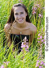 Beautiful brunette woman in grass