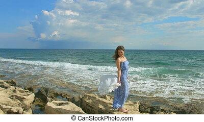 """Beautiful brunette woman in maxi dress enjoying windy day on seashore, vacation"""