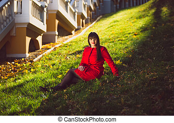 brunette woman in red jacket sitting on grass at autumn forest